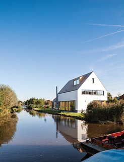 A Modern Take on the Pitched-Roof - Photo 8 of 12 - The newly built house, just feet from the water's edge, occupies the space where a decaying farmhouse once stood.