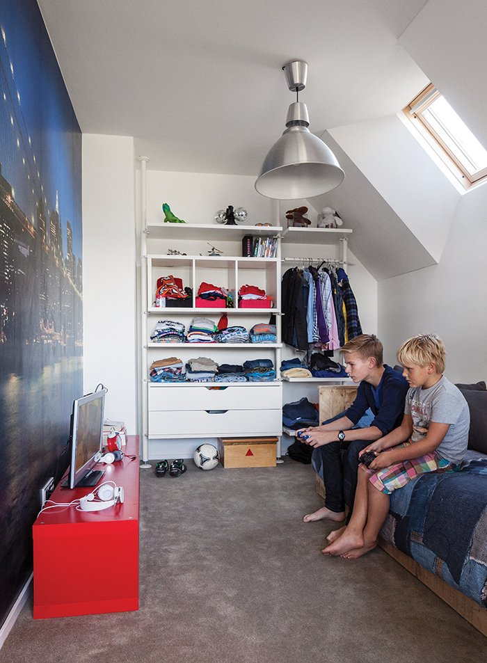 In a family's house in Amsterdam, a New York cityscape takes up one wall in Bram's room, which has furnishings from Ikea and a bed from Goed Gemaakt. Tagged: Kids Room, Bed, Bedroom, Shelves, Pre-Teen Age, Storage, and Boy Gender.  Photo 11 of 13 in A Modern Take on the Pitched-Roof