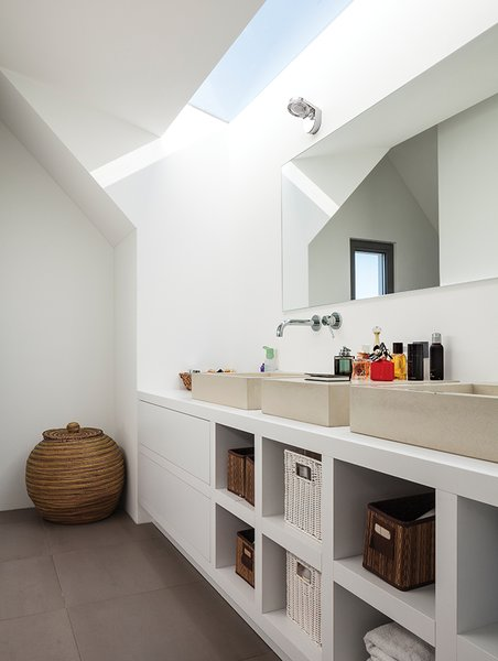 Similar architectural geometries are at play in the ceiling of a bathroom, where custom sinks by Concr3te accompany Grohe fixtures.