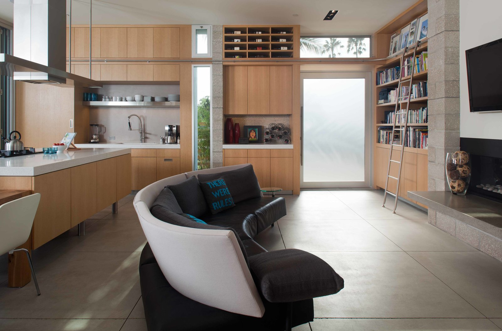 The living room couch—a semi-circle design by Niels Bendtsen—is the centerpiece of the open-plan living space. The rolling kitchen ladder is by Bartels Doors, and the kitchen island, pantry, and cabinets were custom made by Hill Construction Company.