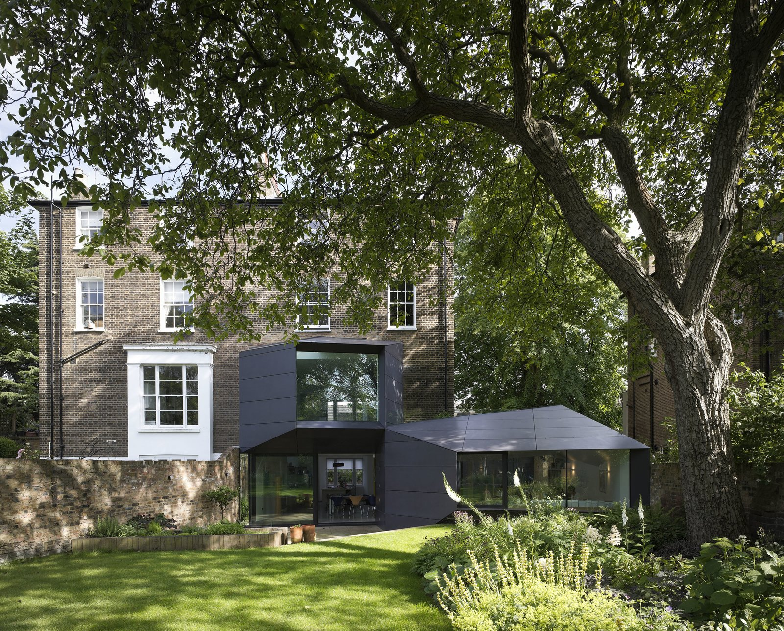 """The roughly 5,000-square-foot Lens House renovation, which was finished in 2012 and just won a 2014 RIBA National Award, required six years, major remedial work on the roof and walls, approval from the planning committee, and even a sign-off from a horticulturalist to guarantee the backyard excavation didn't interfere with a walnut tree. """"These things aren't for people who are in a hurry,"""" says architect Alison Brooks. The focus is the ten-sided trapezoidal office addition. """"It wraps itself around the house with a completely different set of rules than the Victorian building,"""" she says."""