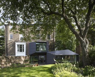 "10 Indoor-Outdoor Homes in London - Photo 9 of 10 - The roughly 5,000-square-foot Lens House renovation, which was finished in 2012 and won a 2014 RIBA National Award, required six years, major remedial work on the roof and walls, approval from the planning committee, and even a sign-off from a horticulturalist to guarantee the backyard excavation didn't interfere with a walnut tree. ""These things aren't for people who are in a hurry,"" says architect Alison Brooks. The focus is the 10-sided trapezoidal office addition. ""It wraps itself around the house with a completely different set of rules than the Victorian building,"" she says."
