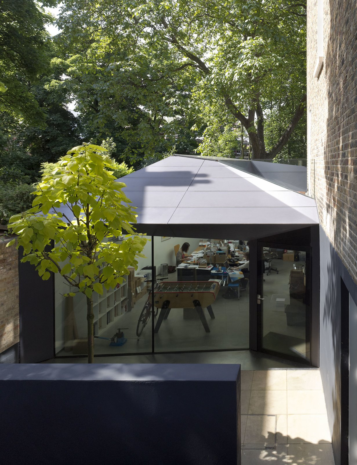 """Backyard excavation created a sunken courtyard, where the side entrance to a new 750-square-foot office space lies. The exterior is clad in Corian, a surface normally found on countertops. """"The clients love that they can go to another wing of the house and have an office,"""" says Brooks. """"There's a physical seperation. We've designed it so in the future, if they close the firm, they can open up the door between the office and the dining room and connect the entire basement floor."""" Tagged: Exterior, Metal Siding Material, and House.  Photo 2 of 7 in Victorian Home in London Gets a Modern Office Addition"""