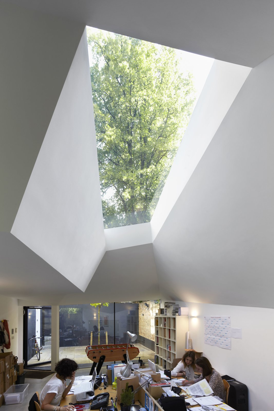 """The abstract geometry of the exterior allows for unique openings and this sklylight, which provides natural light to the staff throughout the day. """"One of my ambitions is to place openings, windows, and roof lights strategically, so you get a sense of the time of day and the weather,"""" says Brooks.  Photo 5 of 7 in Victorian Home in London Gets a Modern Office Addition"""