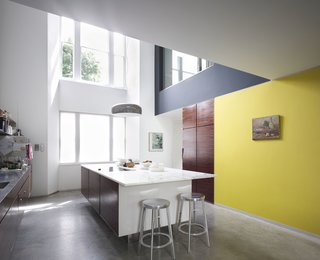 Victorian Home in London Gets a Modern Office Addition - Photo 6 of 7 - The kitchen features a concrete island topped with marble. Deja-Vu stools by Naoto Fukasawa surround the island. A print by Guy Gormley, as well as a painting bought during holiday in St. Tropez, hang on the walls.