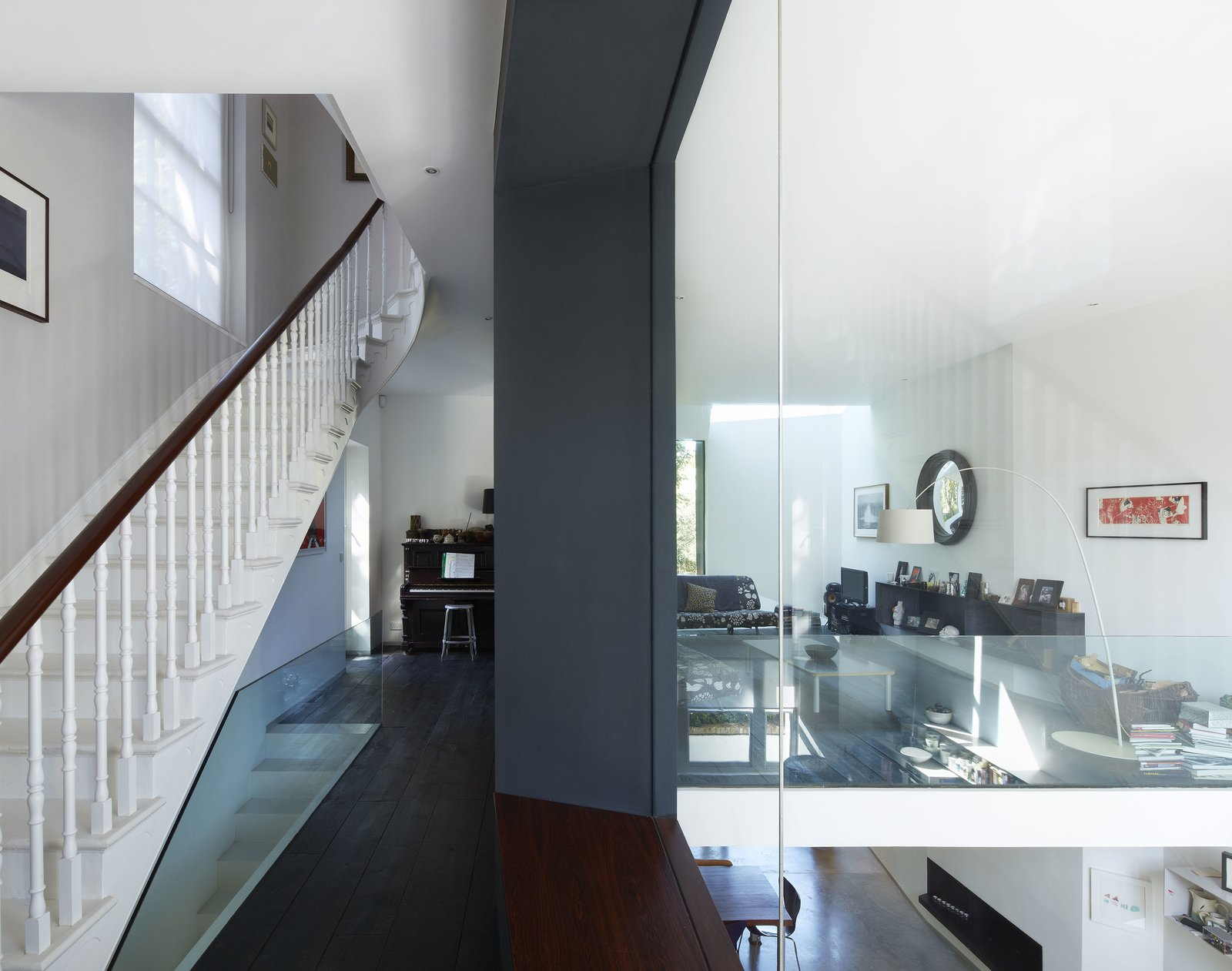 On the mezzanine level, different styles and eras complement each other, from the Georgian staircase to the sheets of glass and the Lola Convex Mirror to the James Irvine sofa.