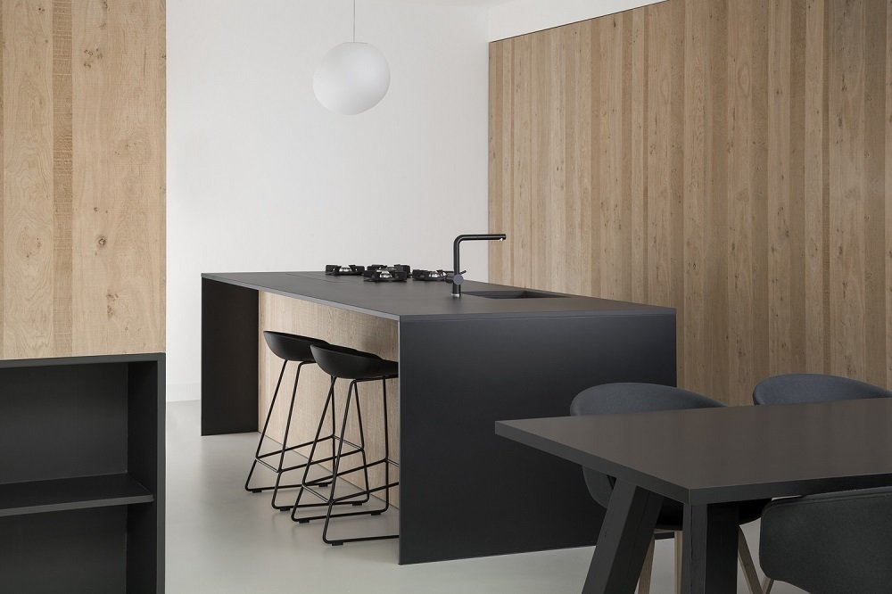 The kitchen features custom cabinetry and a large sliding door, both made from oak, that provides recessed storage space. The black theme continues with the furniture, including HAY About A Stool (AAS 38) models around the kitchen island and the HAY About A Chair (AAC 22) set.  Kitchens by Carl R from Minimal Home Recreates Nature in the Heart of Amsterdam