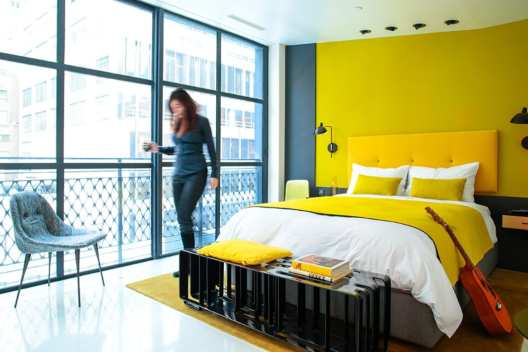 Neutral accents offset bright yellow details in this room.  Photo 5 of 25 in 25 Bold Ways to Decorate with Yellow from Every Room is a Different Hue in This Bright Manhattan Hotel
