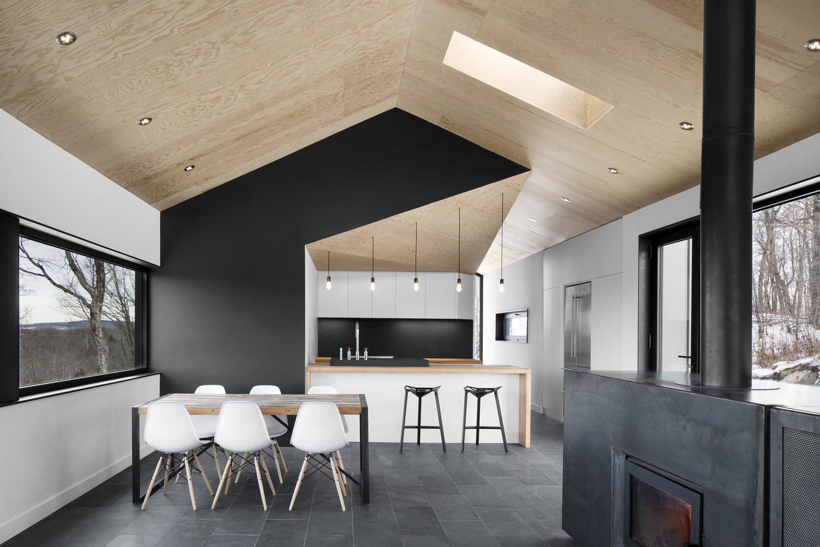"The architects stuck to a gray-scale color palette, installing slate tile floors that softly contrast with the white walls and Eames dining chairs. ""It lets the views out the windows become the focus,"" Dworkind explains. Doses of pure black accent important features, like the central wall that divides the kitchen and master bedroom behind it from the main living space.  Photo 5 of 11 in Amazing Cantilevered Home in the Mountains"