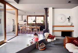 "Simplicity Rules at this Family Beach House Designed to Double as a Rental - Photo 3 of 11 - To instill a soft juxtaposition to the brick and concrete in the house, Nolan specified Hycraft's Carramar wool carpet in the living area. Set a step down, the ""pit,"" as Nolan refers to it, receives the low winter sun but is shielded from harsh summer rays by the deep eaves. The ledge becomes a casual seating area."