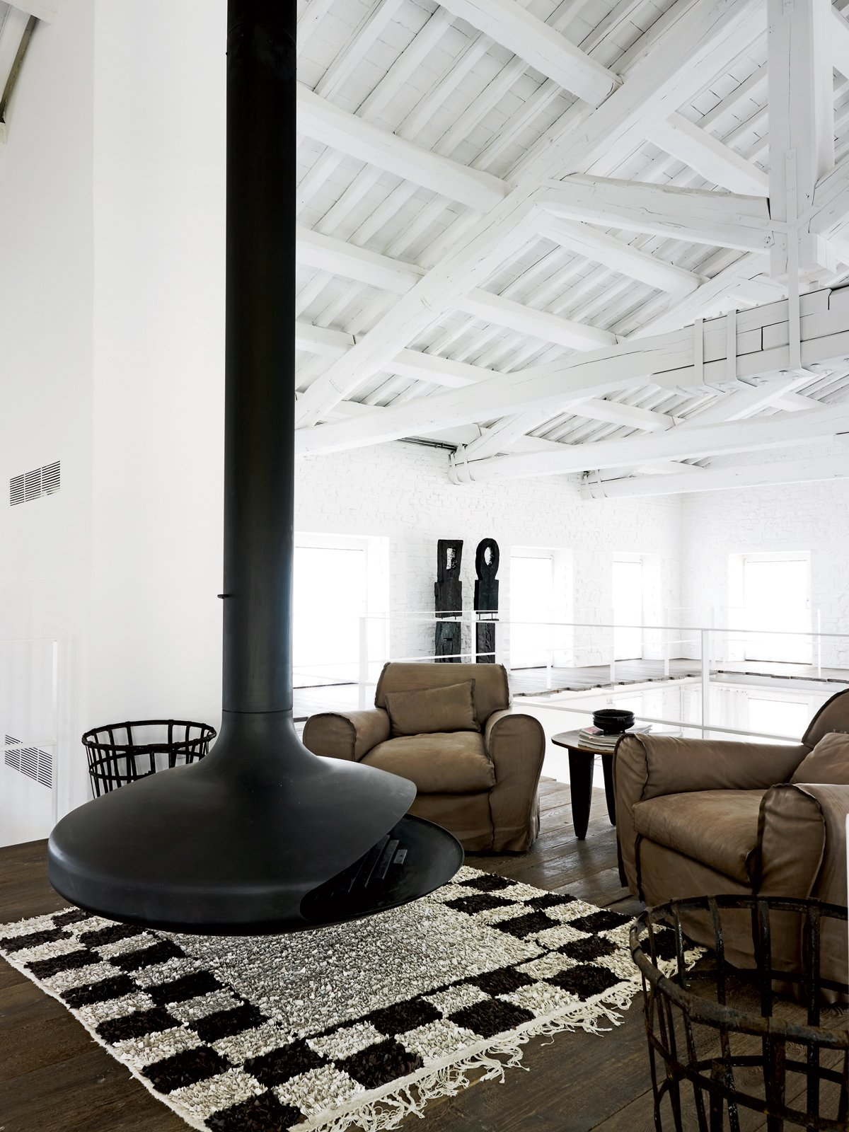 In the upper-level seating area, an Ergofocus fireplace is flanked by a pair of leather armchairs designed by Navone for Baxter  Photo 8 of 11 in Paola Navone's Industrial Style Renovation in Italy