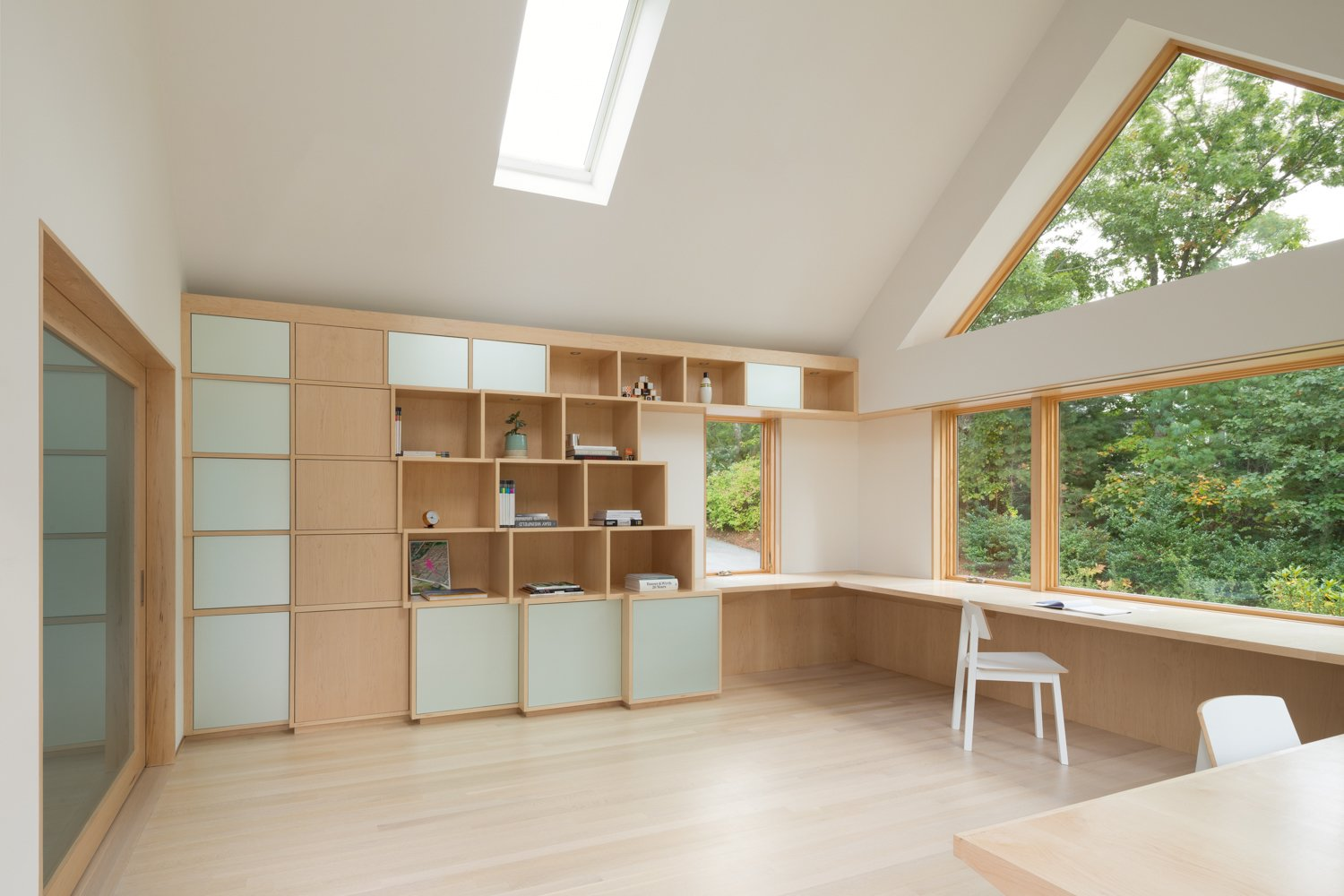 The pixelated shelving system, made of birch and acid-etched mirrored glass, as well as the cantilevered desk, were customized for the Woolford's space. A large glass sliding door framed in white oak separates the addition from the rest of the home. The chairs are from Ikea.  Home Offices and Workspaces We Love by Matthew Keeshin from A Bright Office Addition in Cape Cod