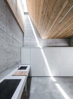 Spotlight on Portugal: 7 Epic Modern Spaces - Photo 7 of 7 - Sunk into a slope beside a stream in Portugal's Caniçada Valley, the rear of this vacation retreat's ground floor is deeply removed from the outdoors. Fortunately, architecture firm Carvalho Araújo found a way to direct natural light into the kitchen by pairing a skylight with a double-height funnel. The narrow band provides just a modicum of illumination, but it's a potent reminder of the scenery on high.