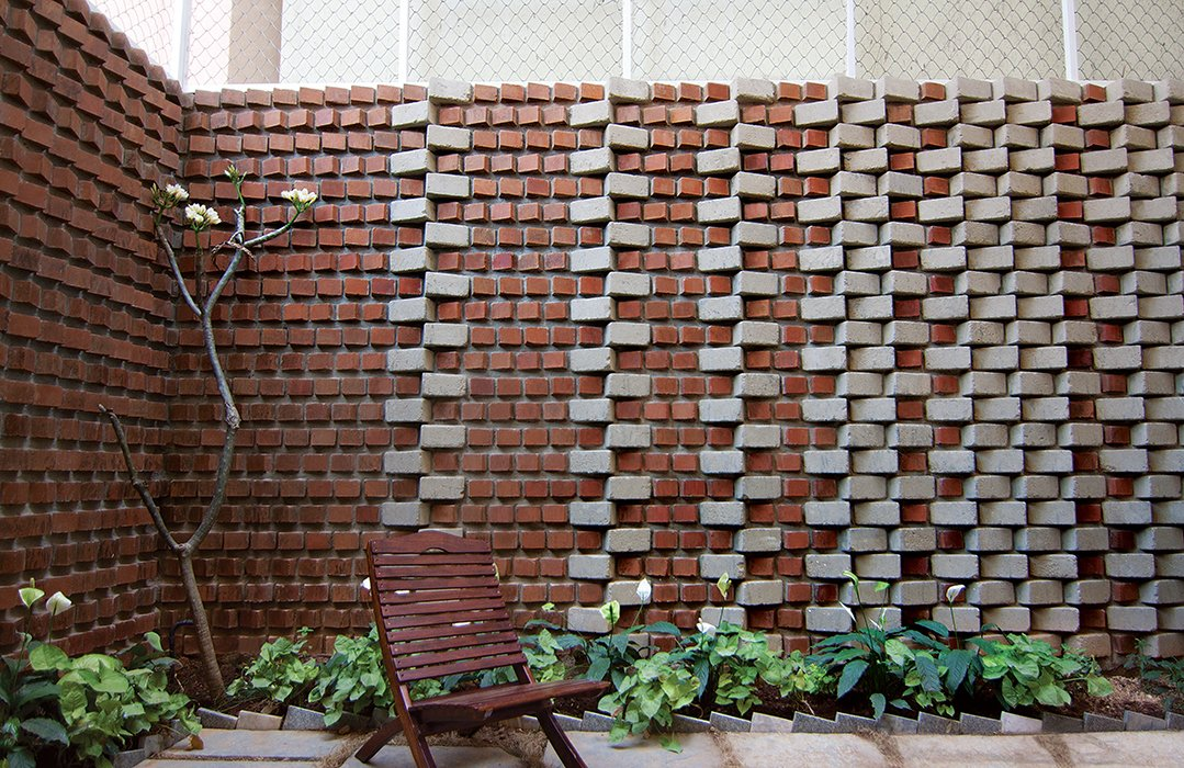 The wall surrounding Ravi and Esha Chowdhary's backyard in Bangalore, India, includes bricks made from soil that was excavated for their home's foundation.