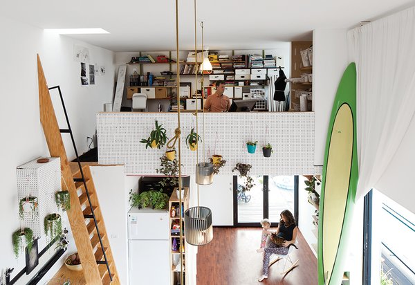 Designer and digital fabricator Shawn Benson shares his 595-square-foot second-floor space with his wife, Jessica, and their daughter, Roux. The 15-foot-high ceilings allow plenty of room for a full-size ocean paddleboard.