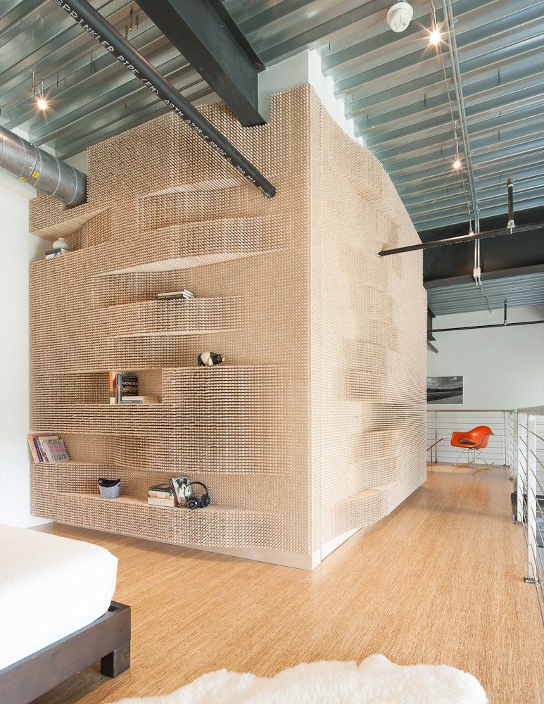 Merge Architects wrapped the peg wall around three sides of a bathroom to hide a door and provide a storage for books and knick knacks. Tagged: Bedroom, Bed, Rug Floor, Track Lighting, Shelves, and Light Hardwood Floor.  Storage by Dwell from Catch A Wave