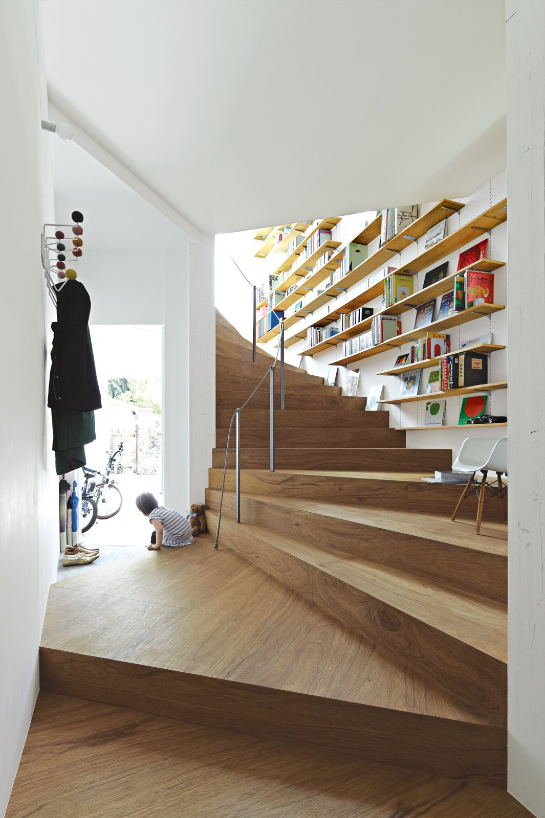 Bookshelves add extra utility to the undulating staircase in Tokyo's 921-square-foot Coil house. The space was designed by architect Akihisa Hirata for Sakura and Ryo Sugiura, a young couple with two children.  Stairs by Jacob Resler from This Sculptural Staircase Shapes an Entire Home