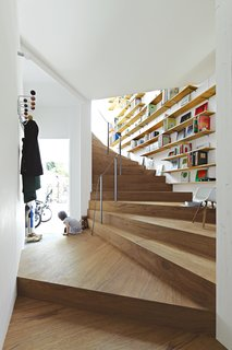 "This Sculptural Staircase Shapes an Entire Home - Photo 3 of 3 - Three-year-old Ran Sugiura peers out the front door of her Tokyo home, a concept-driven yet surprisingly livable piece of architecture that her parents describe as uniquely well suited to the family's flexible ""futon lifestyle."""