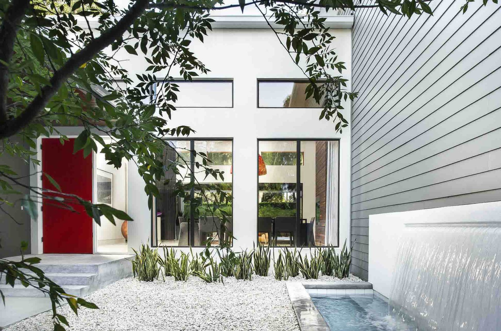 The red door was De Azevedo's idea, says Phil Kean, president of the Phil Kean Design Group. It adds a spash of color to the front courtyard, which is simply landscaped with gravel and low-maintenance plants. A water feature was installed next to the James Hardie fiber-cement siding.