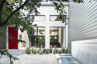 A Modern Home For a Design-Savvy Family in Florida - Photo 2 of 7 - The red door was the homeowner's idea, says Phil Kean, president of the Phil Kean Design Group. It adds a splash of color to the front courtyard, which is simply landscaped with gravel and low-maintenance plants. A water feature was installed next to the James Hardie fiber-cement siding.