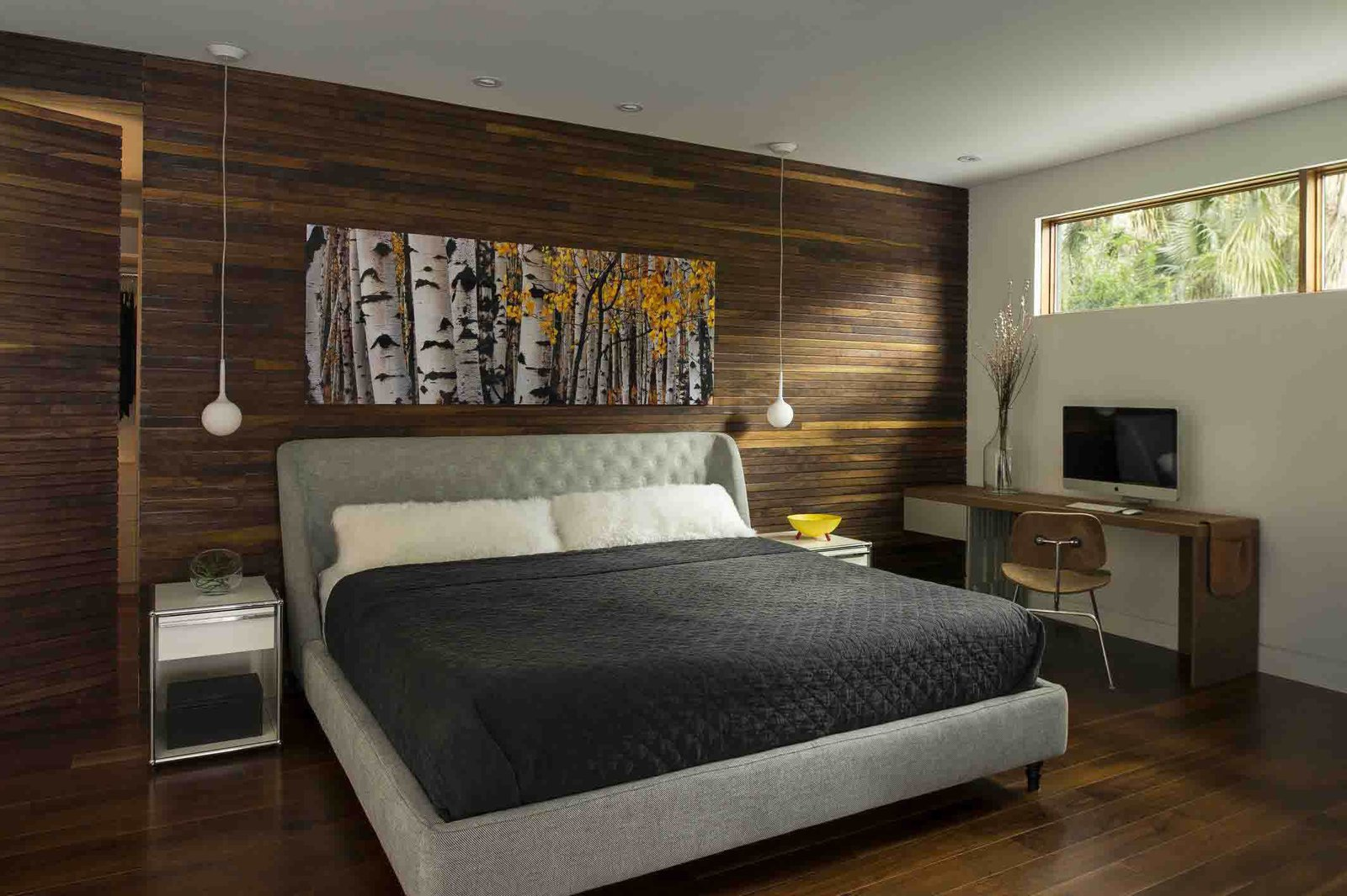 "Wood was used more extensively in the master bedroom. ""I think the intention was just to warm it up and make it more cozy,"" Kean says. A wood-covered ""disappearing door"" cleverly conceals a closet. Tagged: Bedroom and Bed.  Photo 6 of 7 in A Modern Home For a Design-Savvy Family in Florida"