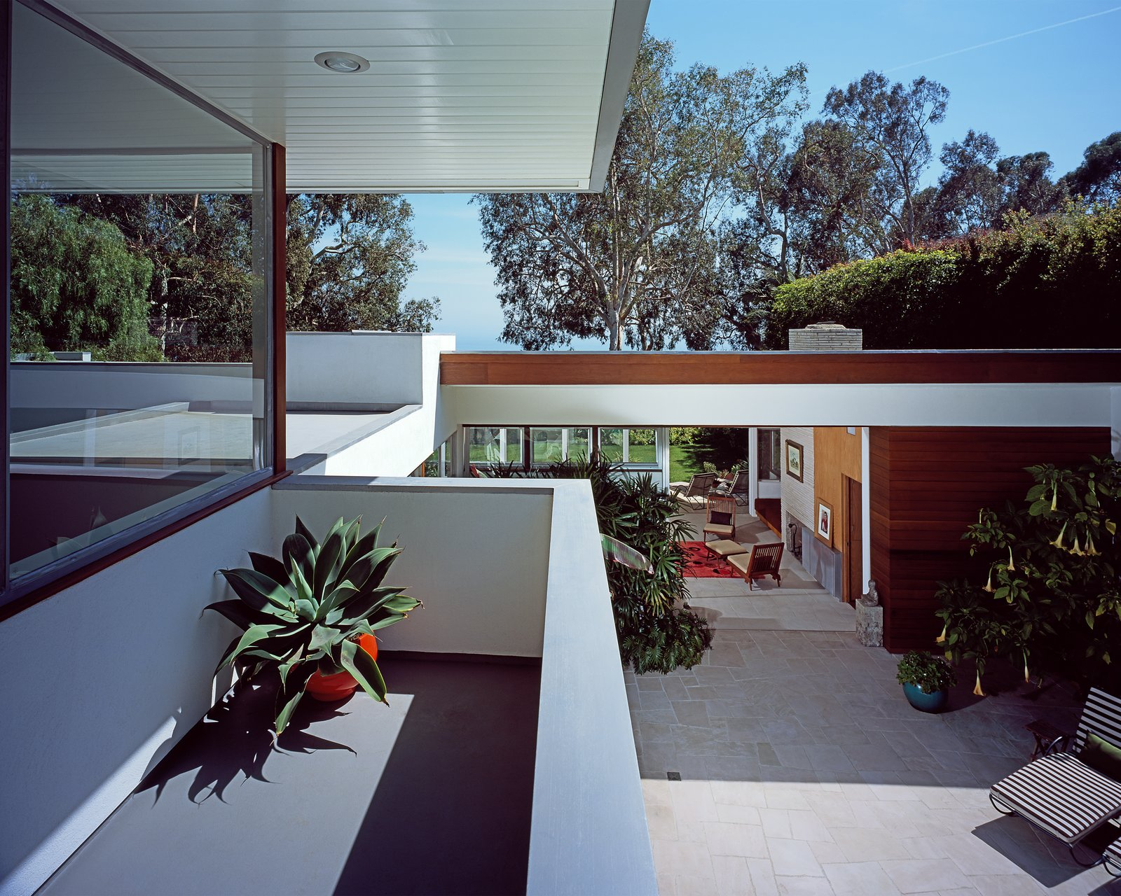 """The original house opens completely to the repaved pool deck, which leads to the upstairs addition. """"Working on the house had only increased our respect for Neutra, whom we had always admired greatly,"""" says Grueneisen. """"So we knew that any major additions would have to be respectful to his design.""""  Photo 3 of 6 in A Neutra Renovation in Los Angeles"""