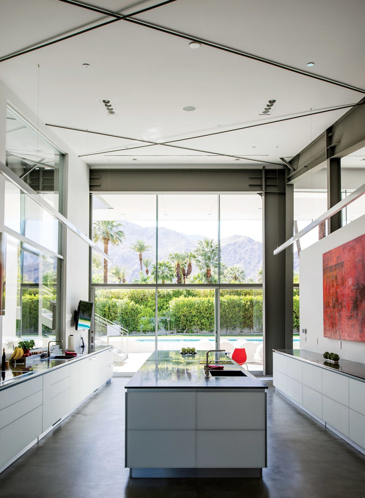 In the kitchen, which faces west to capture views of the San Jacinto Mountains, a large red work by James Jensen punctuates one wall. The induction cooktop is from Gaggenau; the sinks were sourced from Blanco. Tagged: Kitchen, Ceiling Lighting, Concrete Floor, and Recessed Lighting.  Photo 2 of 12 in An Energy-Efficient Hybrid Prefab Keeps Cool in the Palm Springs Desert