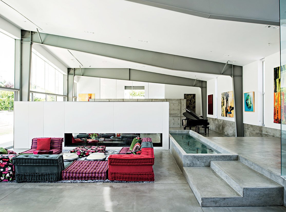 A Mah Jong sofa by Roche Bobois in the living room lends a colorful counterpoint to the custom water feature that runs alongside it.  Innovative Homes from Our Prefab Issue by Allie Weiss from An Energy-Efficient Hybrid Prefab Keeps Cool in the Palm Springs Desert