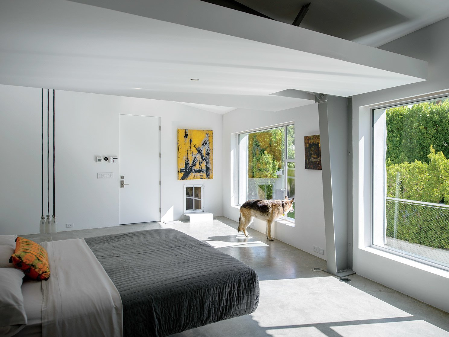 In the master bedroom, a Droog Milk Bottle lamp hangs next to a Fluttua Bed designed by Daniele Lago. An artwork by Brooke Westlund hangs over a custom pet door for the client's dog, Kona. Tagged: Bedroom, Concrete Floor, and Bed.  Photo 2 of 25 in 25 Dogs Living in the Modern World from An Energy-Efficient Hybrid Prefab Keeps Cool in the Palm Springs Desert