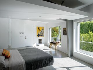 45 Pets in Beautiful Modern Homes - Photo 16 of 45 - In the master bedroom, a Droog Milk Bottle lamp hangs next to a Fluttua Bed designed by Daniele Lago. An artwork by Brooke Westlund hangs over a custom pet door for the client's dog, Kona.
