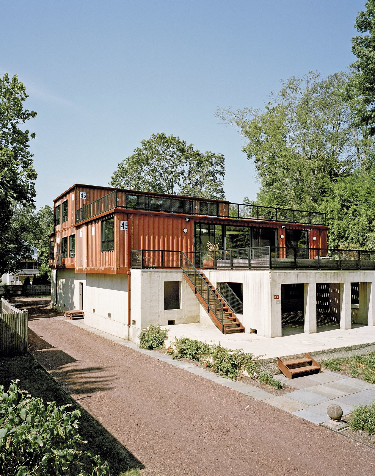 "Purchasing a lot off the Delaware River in Pennsylvania, Martha Moseley and Bill Mathesius adapted an unused concrete foundation—remnants of its previous owner's abandoned plans—to create a home that's uniquely their own. ""We were inspired by the site, and our desire to have something cool and different,"" says Moseley. Tagged: Exterior, Concrete Siding Material, Metal Siding Material, Shipping Container Building Type, House, and Prefab Building Type.  Shipping Containers by Dwell from How to Buy a Shipping Container"