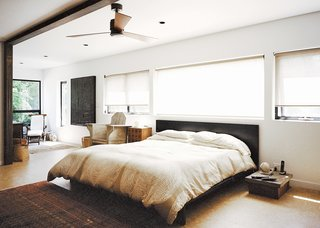 In the master bedroom, a custom bed by Jason Micciche is outfitted with linens from Marimekko; the ceiling fan is by Fanimation.