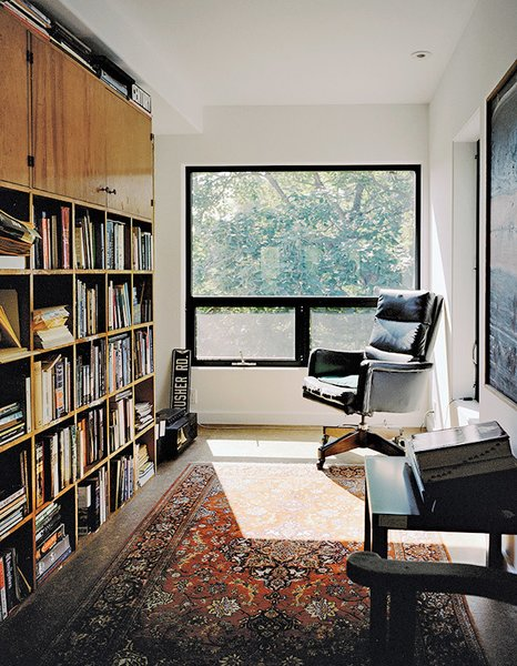 In Mathesius's office on the third floor, an antique armchair, a rug, and a bookshelf made from salvaged wood create a cozy, sun-filled reading nook.