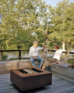 Discover 6 Amazing Riverside Homes - Photo 4 of 12 - The staggering of the shipping containers created a series of decks in the rear of the home, which overlooks the Delaware River. A mix of vintage finds and pieces designed by Mathesius, including a Cor-Ten steel fire pit on the second-floor deck, furnish a majority of the home.