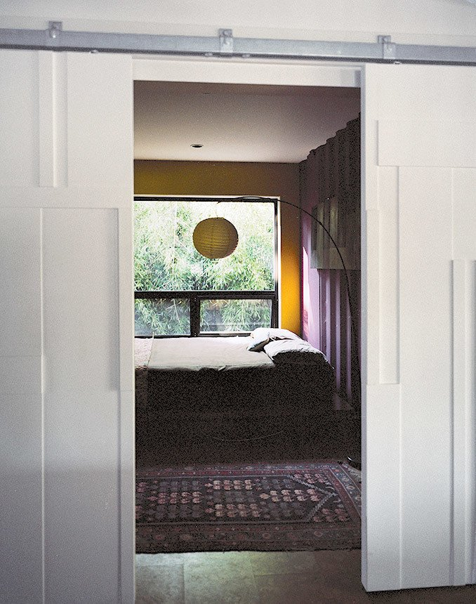 Though many of the interior surfaces have been spray-foam insulated and covered in Sheetrock, the couple, drawn to the natural patina of the shipping containers, opted to keep select areas of the material exposed. Closed off by bas-relief doors designed by Mathesius, the main guest room is one of few spaces that put whole walls of the raw surface on display, painted in Benjamin Moore's warm Kalamata and Wasabi hues. benjaminmoore.com  Photo 11 of 12 in A Shipping Container Home in Pennsylvania Embraces Its Rugged Industrial Origins