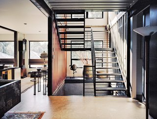 """Moseley notes the home's distinctive staircase as one of her favorite features. """"When the steel was ordered from the steelyard,"""" she says, """"it was marked with our metalworker's name, for easy pickup. That scribble still exists in random places in the staircase and is very industrial—we love it!"""" Hand-welded by Mike Carman, a local contractor, the staircase runs through all three floors, and it was custom-sized to fit the dimensions of the shipping containers, measuring nine-feet-six-inches tall and eight-feet wide."""