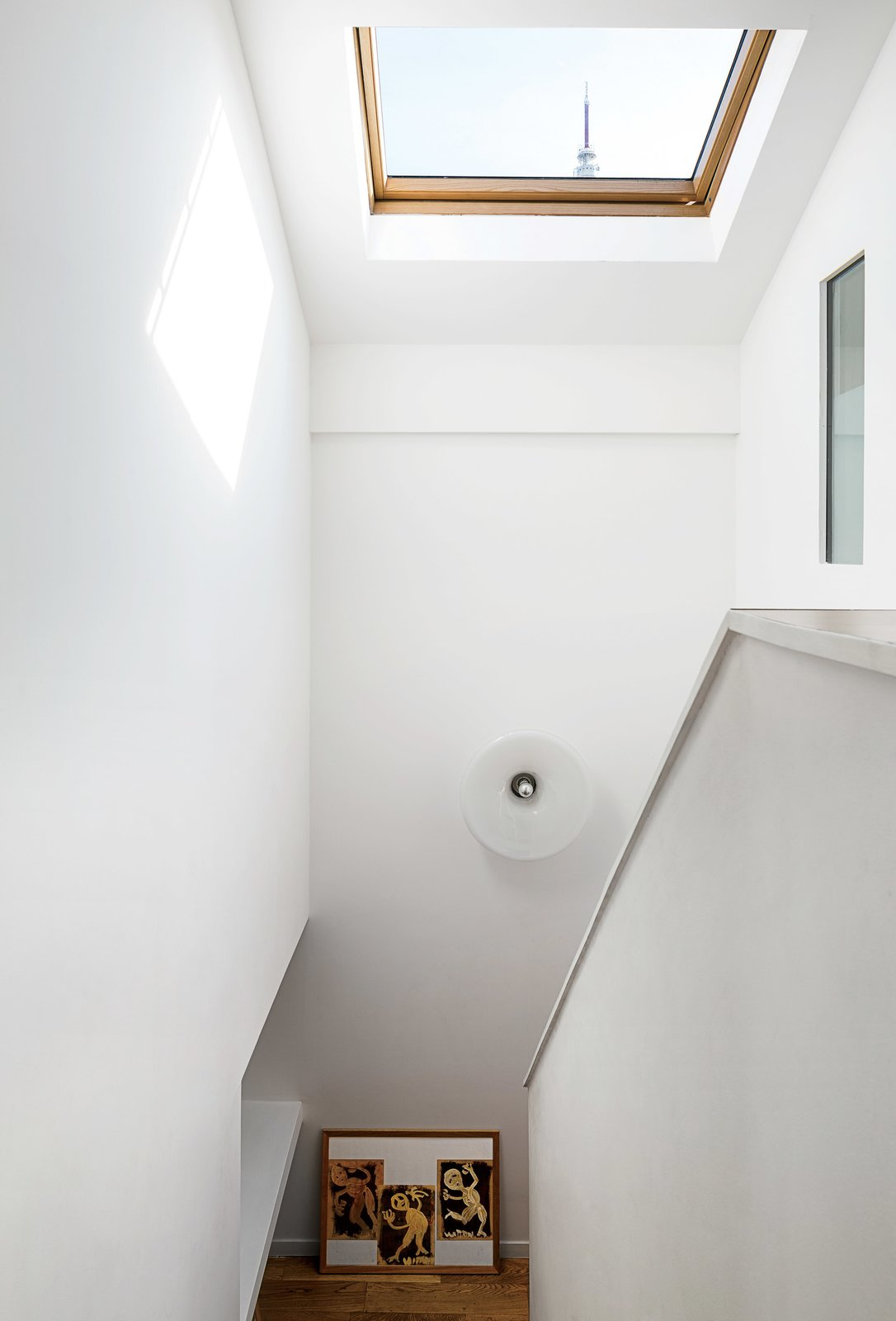 """The antenna of Claude Vasconi's TDF television tower is visible through the Velux skylight architects Caroline Djuric and Mirco Tardio added to a family house in France. """"It's very French, very angular,"""" Djuric says of the renovation. The light fixture was found at a brocante, or vintage market."""