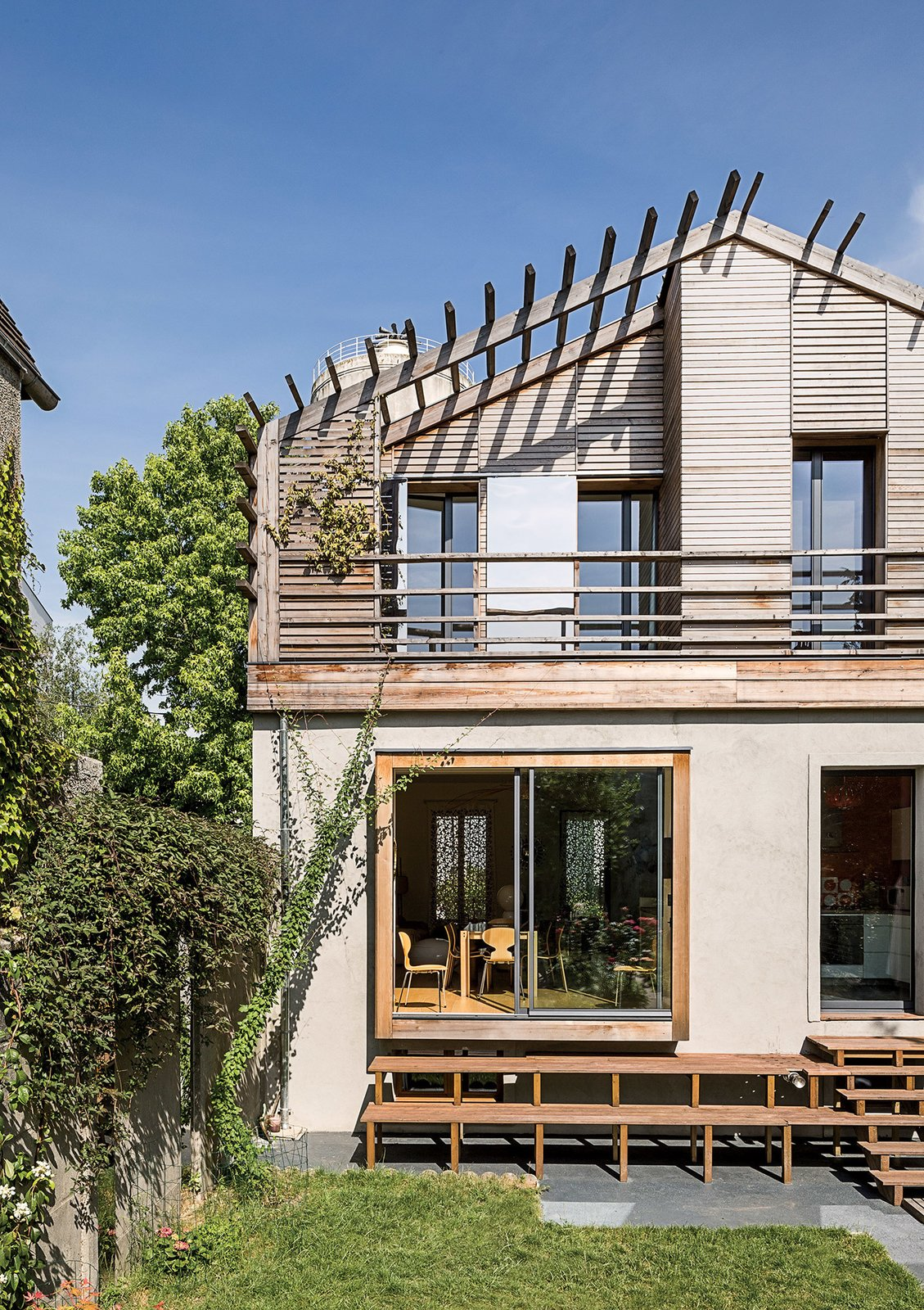 The back of the house was designed as a contemporary counterpoint to the more traditional front facade. The sliding doors and windows are by Technal. An asymmetrical wooden stairway leads down to the garden.  Photo 8 of 10 in 10 Modern Renovations to Unique Homes in France