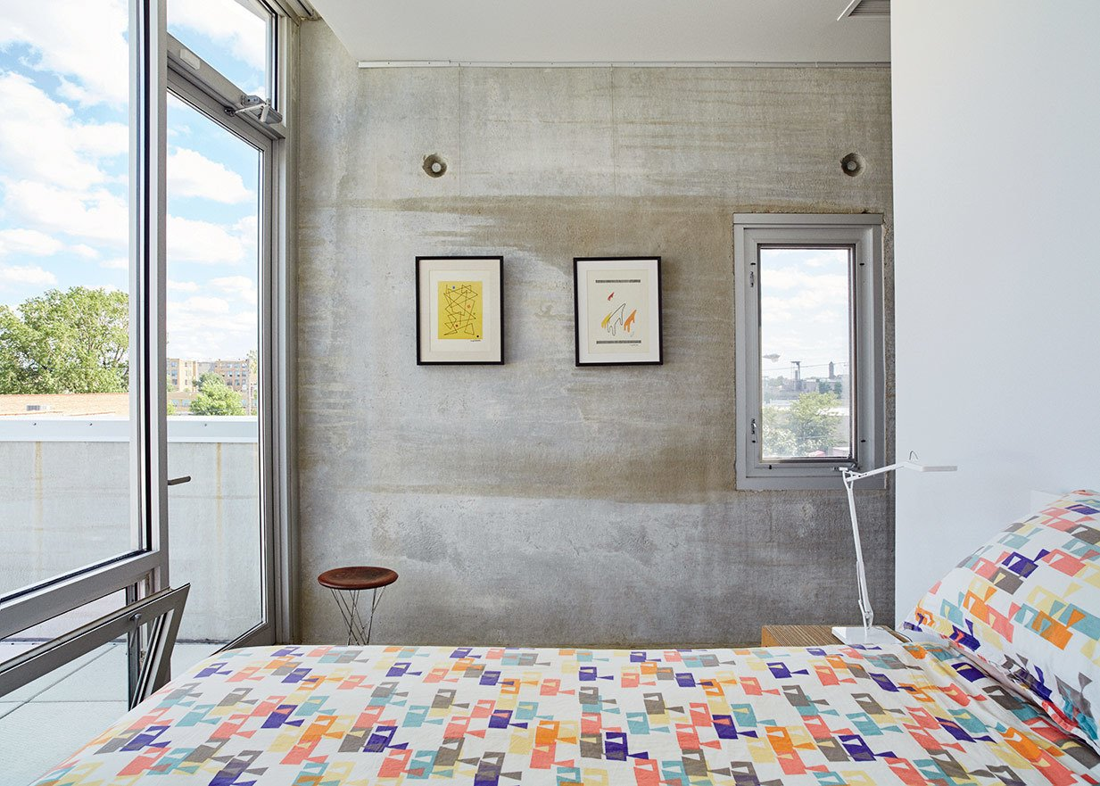 The raw concrete panels serve as a backdrop for the couple's design collection. The bedroom features a Rocking Stool by Isamu Noguchi for Knoll and a Kelvin lamp by Antonio Citterio for Flos.