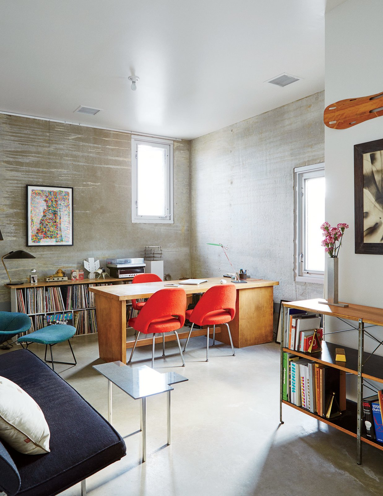 The office is a showcase that includes an Eames Storage Unit for Herman Miller, a wall-mounted Eames leg splint, and chairs by Eero Saarinen and Harry Bertoia for Knoll.  Photo 8 of 9 in In Just 48 Hours, a Chicago Live/Work Space Is Built from the Ground Up Using Concrete Panels
