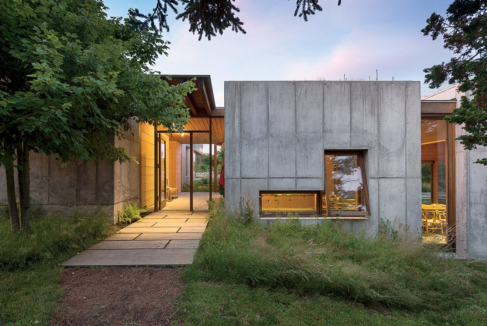 Large, dramatic openings bring transparency and contrast to the 10-inch-thick concrete facade, framing perspectival views of the landscape. Tagged: Exterior, House, and Concrete Siding Material.  Photo 2 of 11 in Six Concrete Boxes Make a Jaw-Dropping Martha's Vineyard Home