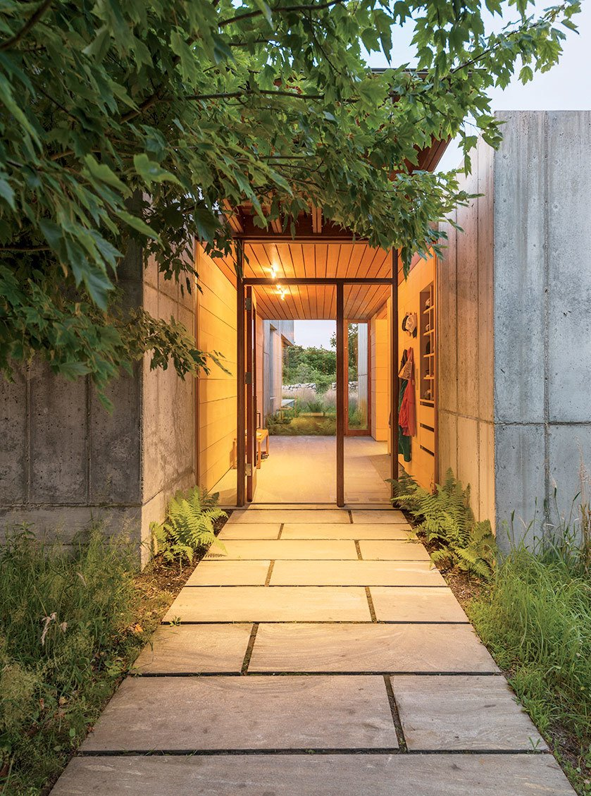 A palette of stone, concrete, and greenery greets guests at the home's front entrance.  Photo 7 of 11 in Six Concrete Boxes Make a Jaw-Dropping Martha's Vineyard Home