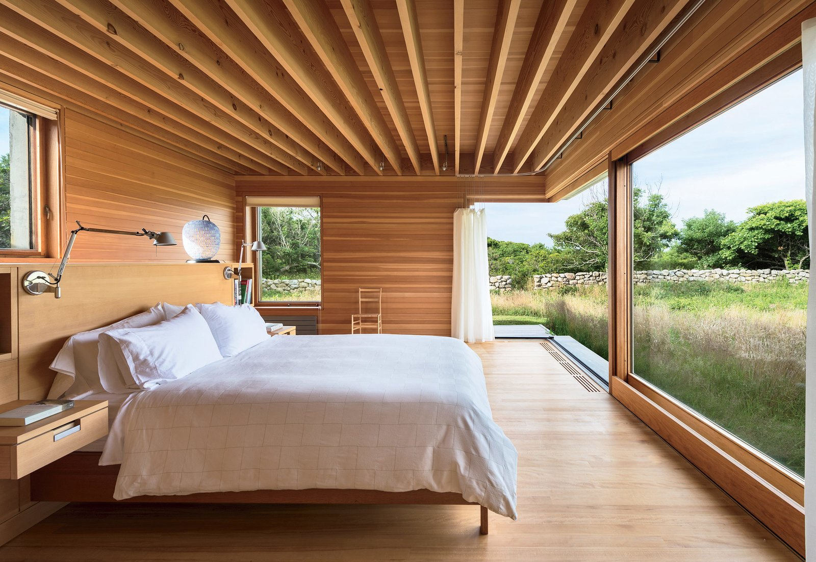Large windows and sliding doors with maximal operability are placed throughout, including the master bedroom, where expansive lift-and-slide mechanisms line three exterior walls. The room is furnished by a custom mahogany headboard and bed frame by Larry Hepler and a glass Murano lamp by Massimiliano Schiavon. Tagged: Bedroom, Bed, Wall Lighting, and Medium Hardwood Floor.  Photo 8 of 11 in Six Concrete Boxes Make a Jaw-Dropping Martha's Vineyard Home