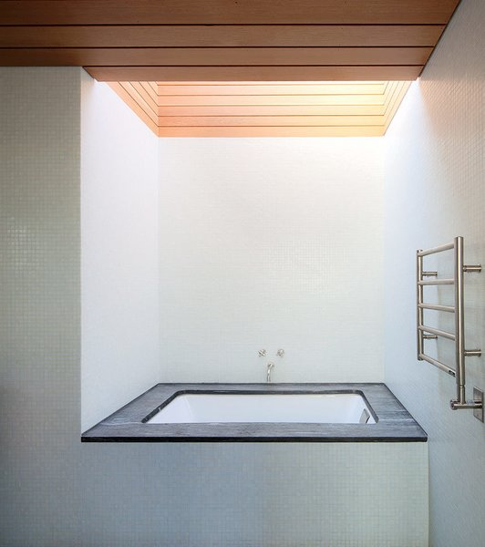 A large skylight looms above a Duravit tub and a Runtal Radia towel warmer in the en suite bathroom.