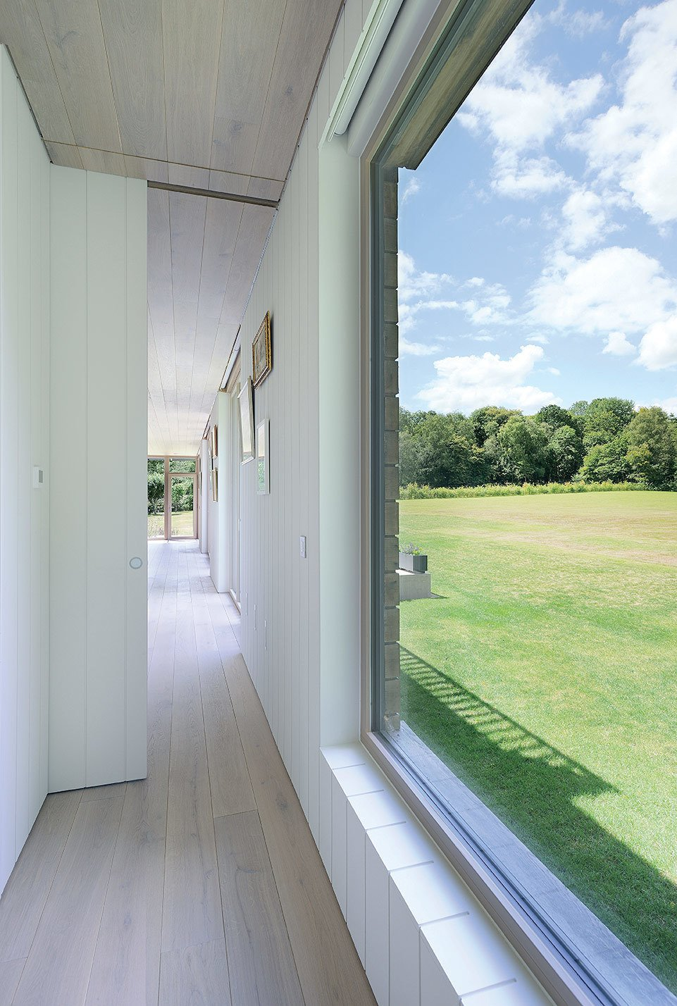 With expansive EcoHaus Internorm windows, the space feels larger than its 1,400 square feet. Tagged: Hallway and Light Hardwood Floor.  Best Photos from A Modern Mobile Home Dropped in Place by Crane