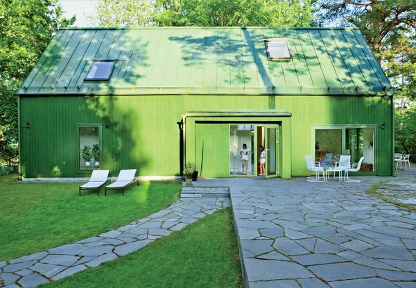 """""""How would a kid draw a house?"""" architect Per Franson asked himself when designing the Olivero-Reinius family home in suburban Stockholm. The simple prefab structure's unusual color comes from a traditional source: falu rödfärg, the historic mineral paint that gives the region's famous barns their red color. Here, the addition of a tint created a hue that matched the house's green Plannja roof panels."""