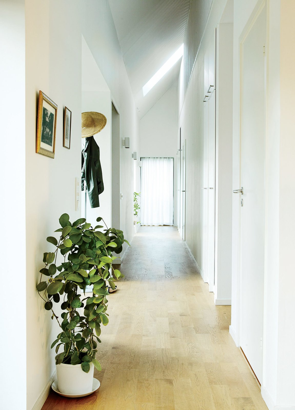 A double-height corridor runs the length of the house, and a slatted wall on the second floor overlooks the space. This Bright Green Prefab in Sweden Looks Just Like a Monopoly House - Photo 2 of 12