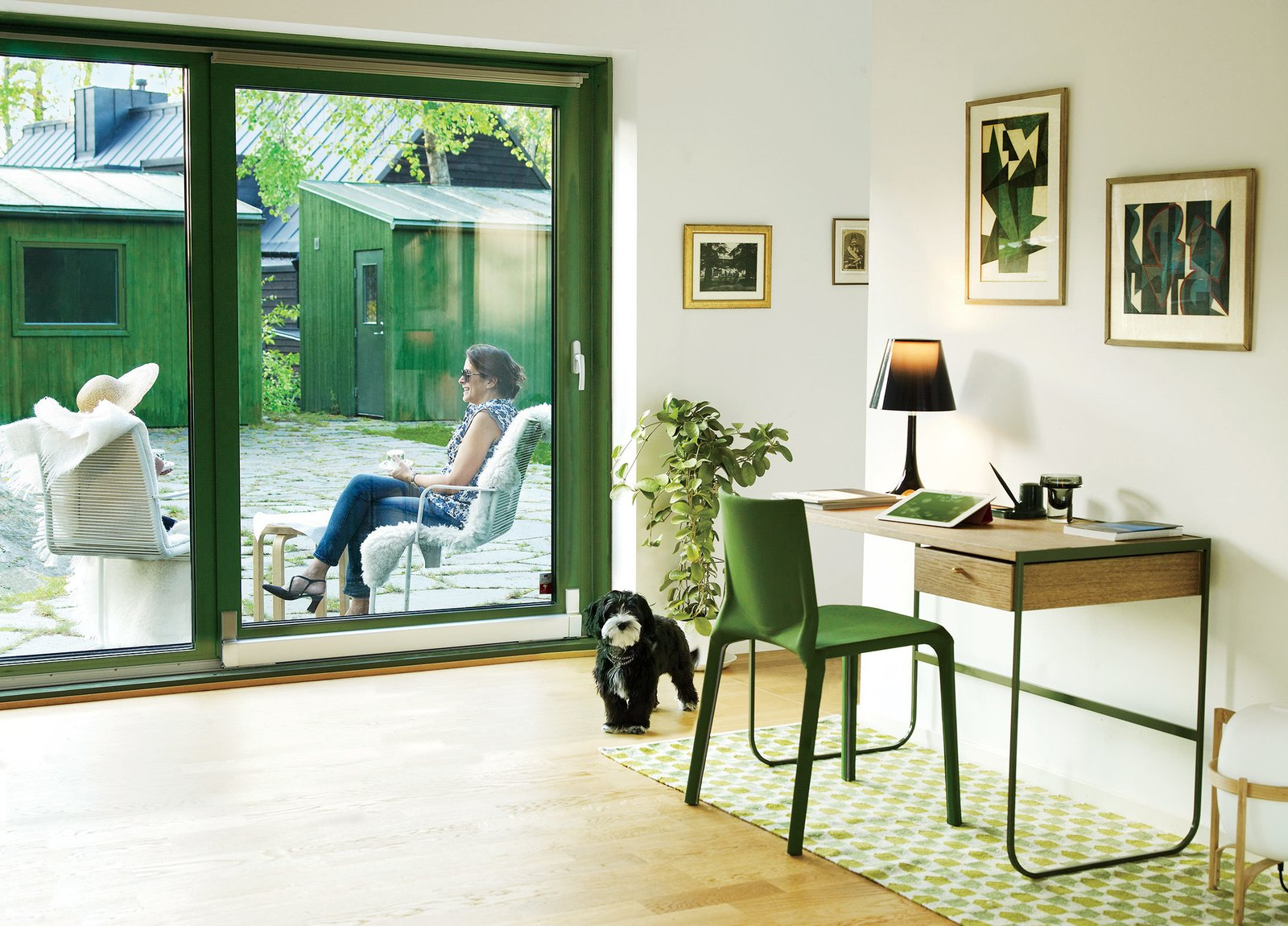 Franson Wreland also designed the court-yard and a pair of 160-square-foot outbuildings—one is used as guest quarters and the other as storage space. While residents Julia and Fatima Olivero-Reinius chat outdoors, Chippie the dog approaches an Asplund desk and a chair by LucidiPevere.