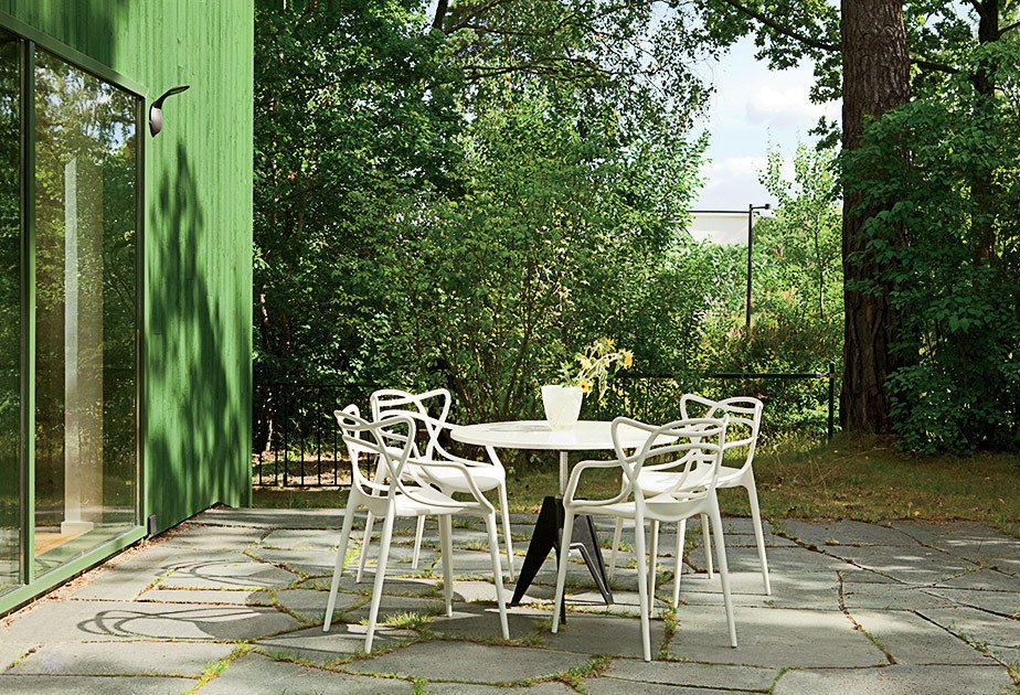 Outside, Kartell Masters chairs surround a Tom Dixon Screw table.  Photo 5 of 12 in This Bright Green Prefab in Sweden Looks Just Like a Monopoly House