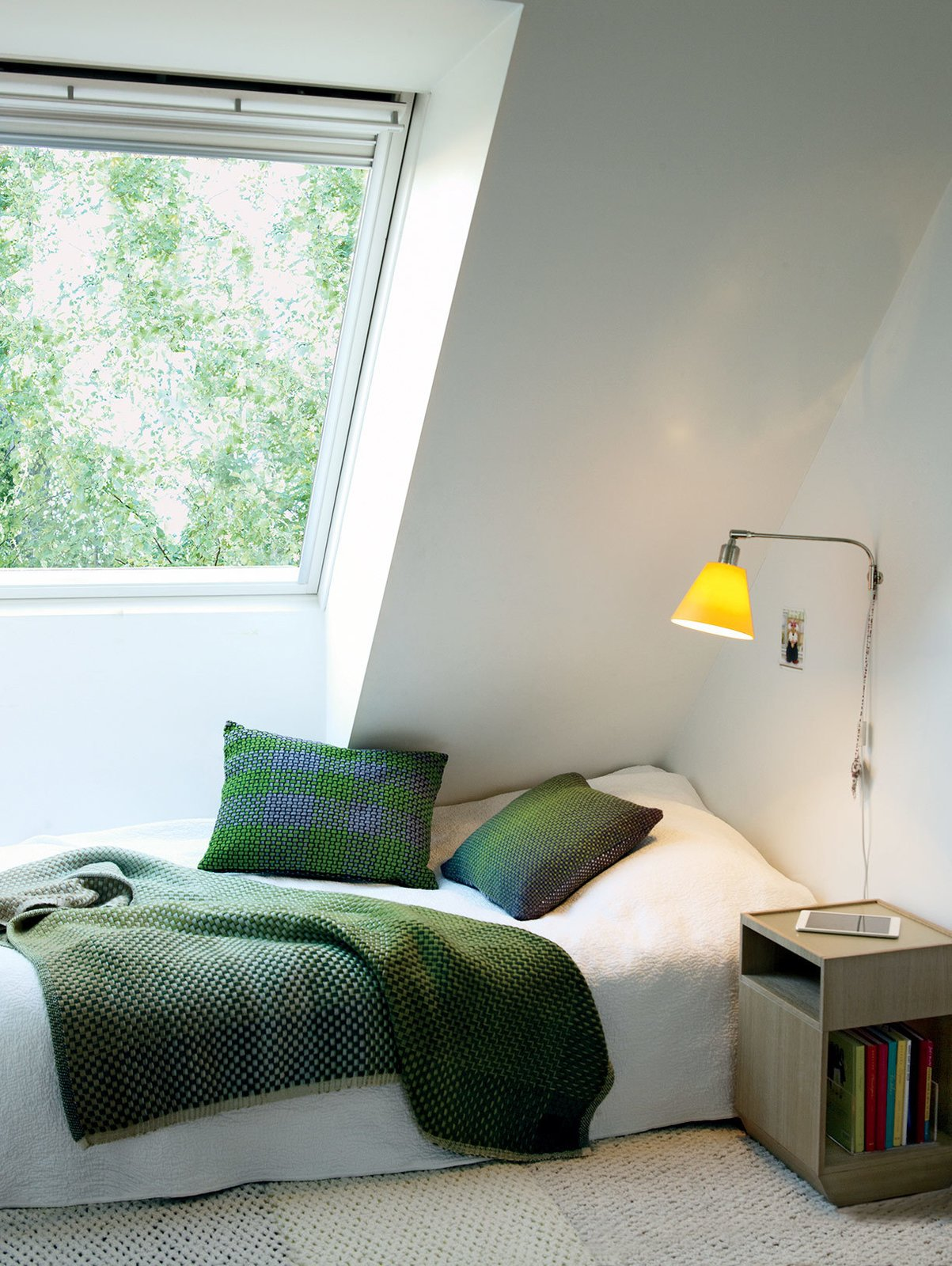 Upstairs, each daughter's bedroom was designed as a sanctuary, with cozy touches like Simon Key Bertman quilts and cushions. The bed and Pile bedside table by Jessica Signell Knutsson sit on top of a Carpet Honeycomb by designer Maria Löw. Tagged: Bedroom and Bed.  Photo 8 of 12 in This Bright Green Prefab in Sweden Looks Just Like a Monopoly House
